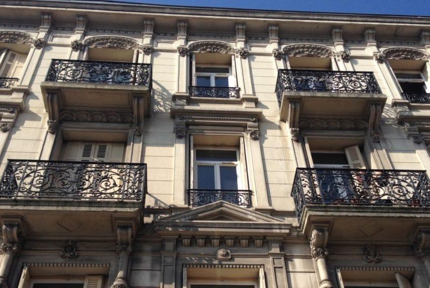 Façade de l'immeuble de type Haussmannien avec balcons individuels.