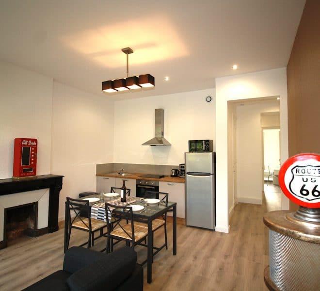 Pièces à vivre espace repas avec cuisine équipée, vaiselle, électroménager, table et cheminée.