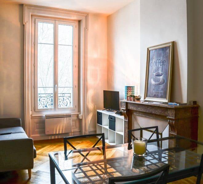 Coin salon télé avec cheminée, table et grande fenêtre.